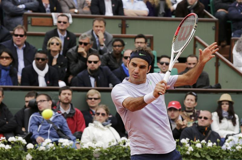 Federer of Switzerland hits a return to Carreno-Busta of Spain during their men's singles match at the French Open tennis tournament in Paris