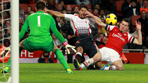 Liverpool Luis Suarez and Arsenal Laurent Koscielny in action